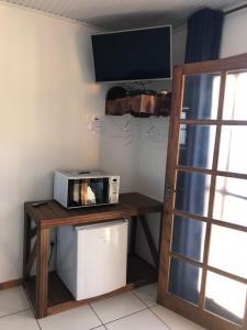 Uma TV ou centro de entretenimento em Pousada do Coqueiro
