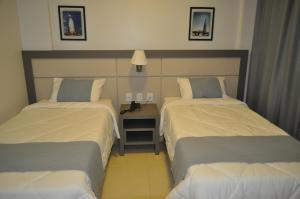 A bed or beds in a room at Hospedare Hotel