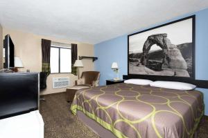 A bed or beds in a room at Super 8 by Wyndham Logan