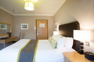 A bed or beds in a room at Breckland Lodge
