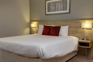 A bed or beds in a room at Best Western Plus Oxford Linton Lodge