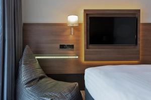 A bed or beds in a room at Moxy Amsterdam Houthavens