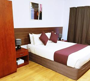 A bed or beds in a room at Airport Garden Inn Hotel & Conference Centre