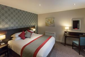 A bed or beds in a room at Best Western Plus Pinewood on Wilmslow