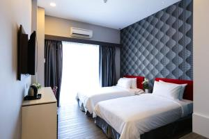 A bed or beds in a room at Cenang Plaza Beach Hotel