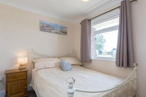 A bed or beds in a room at Sunbeach Holiday Homes