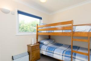 A bunk bed or bunk beds in a room at Sunbeach Holiday Homes