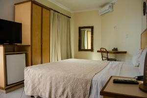 A bed or beds in a room at Via Mar Praia Hotel