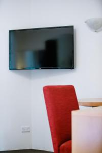 A television and/or entertainment center at Garden Lodge Sydney Hotel
