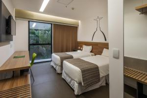 A bed or beds in a room at Linx Galeão