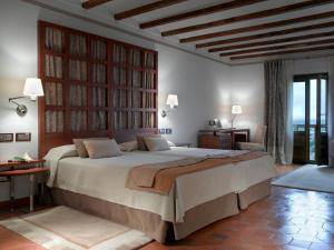 A bed or beds in a room at Parador de Toledo