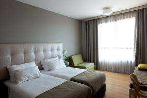 A bed or beds in a room at Shefayim Kibbutz Hotel
