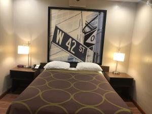 A bed or beds in a room at Super 8 by Wyndham Jamaica North Conduit