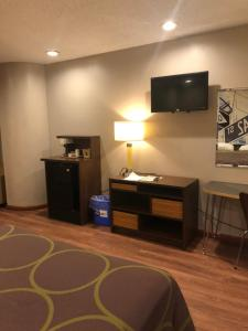 A television and/or entertainment center at Super 8 by Wyndham Jamaica North Conduit