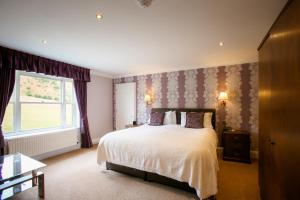A bed or beds in a room at The Izaak Walton Hotel