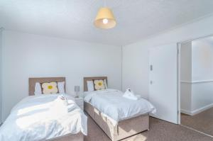 A bed or beds in a room at 6 Bedroom Terraced House - Chatham