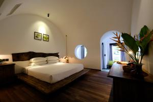 A bed or beds in a room at Hoi An Trails Resort & Spa