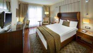 A bed or beds in a room at Titanic City Taksim