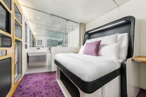 A bed or beds in a room at YOTELAIR London Heathrow Airport
