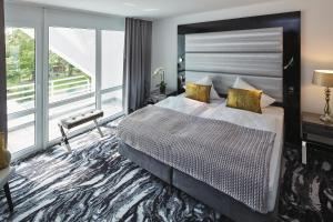 A bed or beds in a room at Kurhaus Design Boutique Hotel