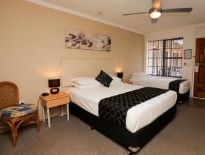 A bed or beds in a room at Bella Villa Motor Inn