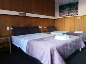 A bed or beds in a room at Jasper Motor Inn