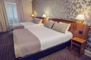A bed or beds in a room at Timhotel Le Louvre