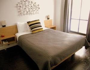 A bed or beds in a room at Touchstone Hotel - City Center
