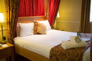 A bed or beds in a room at Best Western Gables Hotel