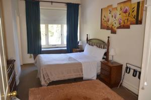 A bed or beds in a room at Leura House
