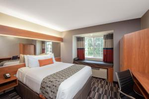 A bed or beds in a room at Microtel Inn & Suites by Wyndham Springfield