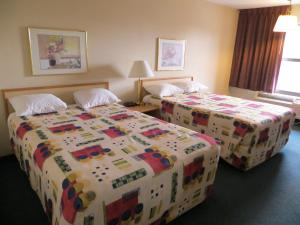 A bed or beds in a room at Homestyle Inn and Suites Springfield