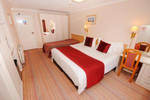 A bed or beds in a room at Denewood Hotel