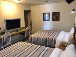 A bed or beds in a room at Village Inn Motel