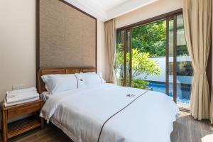 A bed or beds in a room at Sanya Haitang Bay Mushe Villa