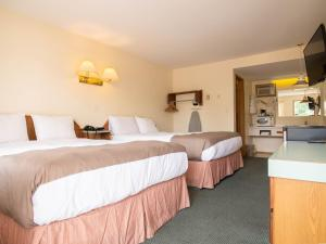 A bed or beds in a room at The Ranchland Inn Kamloops