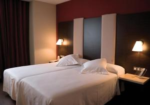 A bed or beds in a room at Hotel Agustinos