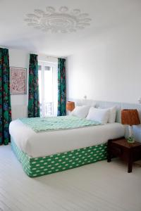 A bed or beds in a room at Hôtel du Temps