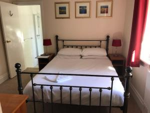 A bed or beds in a room at The Admirals Inn Guest House