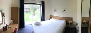 A bed or beds in a room at The Abbey Hotel and conference centre