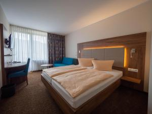 A bed or beds in a room at Hotel Villa am Rhein