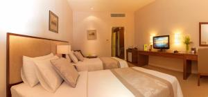 A bed or beds in a room at Catina Saigon Hotel