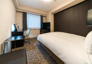A bed or beds in a room at Daiwa Roynet Hotel Nagoya Eki Mae