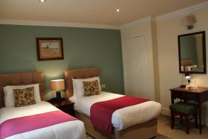 A bed or beds in a room at The Dibbinsdale Inn