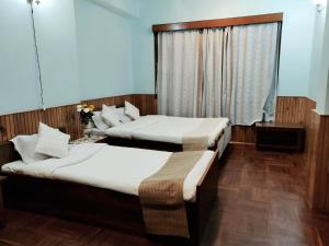 A bed or beds in a room at Tsechu Homestay