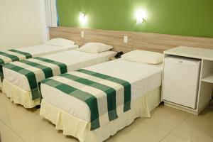 A bed or beds in a room at Vela Branca Praia Hotel
