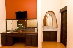 Una televisión o centro de entretenimiento en Hotel & Motel Hacienda Jiutepec