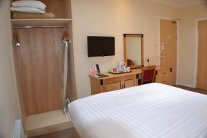 A bed or beds in a room at Chichester Park Hotel