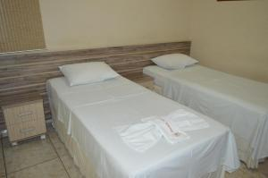 A bed or beds in a room at Pousada Ayrumã