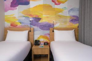 A bed or beds in a room at Ibis Styles Hobart